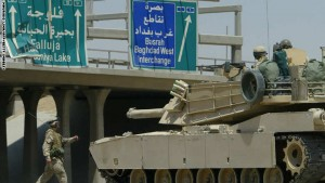 FALLUJAH, IRAQ:  Lieutenant Colonel Gregg Olson (L), from 2nd Battalion, 1st Marines, walks in front of his Abrams tank as it takes  position on the highway at the main entrance of Sunni Muslim flashpoint town of Fallujah, 50kms west of Baghdad, 24 June 2004.  A US Cobra helicopter was shot down near Fallujah after insurgents opened fire with rocket-propelled grenades, mortars and machine-guns at 7:30 AM local time. According to a marine officer, 15 Iraqis were killed, a few marines were wounded and some 200 US marines were involved in the operation.   AFP PHOTO/Mauricio LIMA  (Photo credit should read MAURICIO LIMA/AFP/Getty Images)