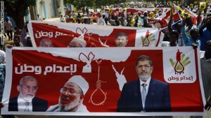 Hundreds of Sudanese Islamists hold posters bearing portraits of Egypt's ousted president Mohamed Morsi (R), Egyptian Muslim Brotherhood leader Mohamed Badie (L) and prominent Qatar-based cleric Yusuf al-Qaradawi as they march towards a United Nations office in central Khartoum on May 22, 2015, to protest the death sentence handed out to Morsi and dozens of other co-defendants by a court in Cairo on May 16. Morsi was among more than 100 defendants ordered by an Egyptian court to face the death penalty for their role in a mass jailbreak during the 2011 uprising. AFP PHOTO / ASHRAF SHAZLY        (Photo credit should read ASHRAF SHAZLY/AFP/Getty Images)
