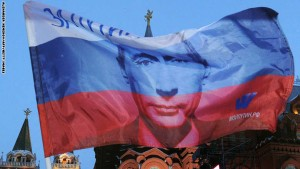 A Russian flag featuring  Prime Minister Vladimir Putin flies above his supporters as they celebrate Putin's victory as they rally at the central Manezhnaya Square just outside the Kremlin in Moscow, March 5, 2012. Police said that  some 15,000 people were taking part in a rally in support of the Russian strongman outside the Kremlin walls.   AFP PHOTO / ALEXANDER NEMENOV (Photo credit should read ALEXANDER NEMENOV/AFP/Getty Images)