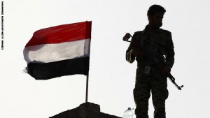"""A Yemeni Shiite Huthi rebel stands next to a national flag in the capital Sanaa on September 21, 2015, during a ceremony marking a year since the city's seizure. The Huthis declared September 21 a public holiday to mark the """"revolution"""" as they sent a delegation to Oman for renewed consultations with UN special envoy Ismail Ould Cheikh Ahmed.  AFP PHOTO / MOHAMMED HUWAIS        (Photo credit should read MOHAMMED HUWAIS/AFP/Getty Images)"""