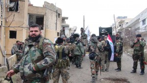 Forces loyal to the Syrian regime stand on a street with national flags after Syria's army and allied forces took full control from rebel groups of the strategic town of Salma, in the northwestern province of Latakia on January 12, 2016.  In a breaking news flash, state television reported that the army, backed by the pro-government National Defence Forces militia, had also seized hilltops surrounding the town.   / AFP / STRINGER        (Photo credit should read STRINGER/AFP/Getty Images)