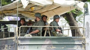 """Tunisian soldiers sit on a truck as they monitor the area of the Bouchoucha army barracks in Tunis on May 25, 2015 after a soldier opened fire at his colleagues. A Tunisian soldier killed some of his comrades and wounded others in a shooting at the barracks near parliament but it was not a """"terrorist"""" attack, the interior ministry said. AFP PHOTO / FETHI BELAID        (Photo credit should read FETHI BELAID/AFP/Getty Images)"""