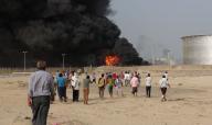 أشخاص يتجمعون في موقع اشتعال نيران بسبب قذائف أطلقها مقاتلون حوثيون على صهاريج تخزين النفط في عدن يوم 27 يونيو حزيران 2015 - رويترز